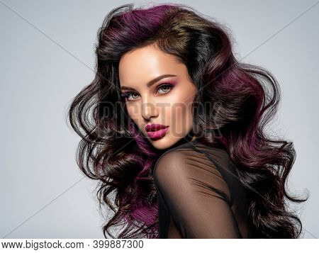Portrait of beautiful young woman with bright maroon makeup. Beautiful brunette with bright cherry lipstick on her lips. Girl with long black hair. Brunette with brightly colored hair. Sexy girl
