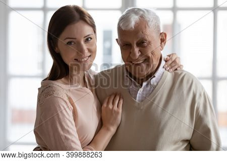 Happy Older Father And Grown Daughter Hugging Looking At Camera
