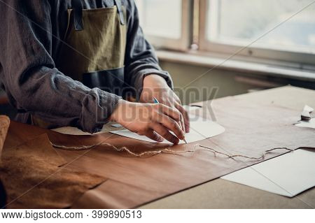 A Young Guy In A Leather Workshop Transfers A Pattern From Paper To Leather.