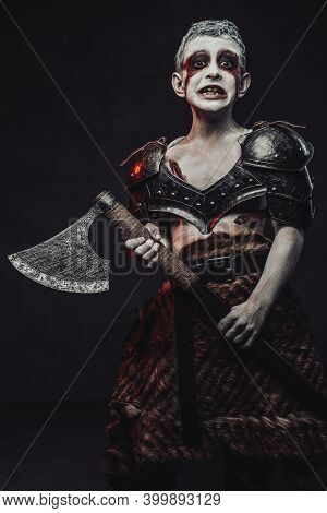 Horror Portrait Of A Kid With Painted Skin Warrior Dressed In Dark Armour And Holding An Axe In Dark