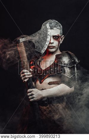 Portrait Of A Boy Soldier With Painted Skin Dressed In Light Armour Posing With Axe In Dark Backgrou