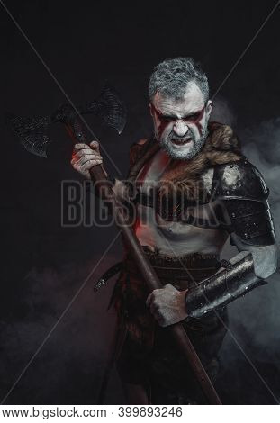 Dressed In Dark Armour With Fur Muscular Mythical Barbarian With Painted Skin And Holding Axe In Dar