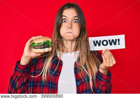 Beautiful caucasian woman eating a tasty classic burger holding wow text puffing cheeks with funny face. mouth inflated with air, catching air.