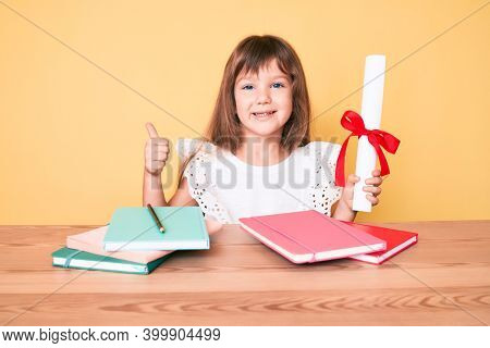 Little caucasian kid girl with long hair holding graduate degree diploma for preschool smiling happy and positive, thumb up doing excellent and approval sign