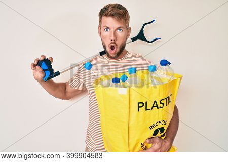 Young caucasian man holding recycling bag with plastic bottles and waste picker afraid and shocked with surprise and amazed expression, fear and excited face.