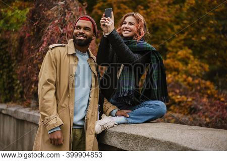 Multinational pleased couple smiling and taking photo on mobile phone at city street