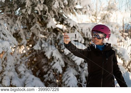 A Young Woman In Skiing Clothes, A Pair Of Ski Goggles And A Ski Helmet Making A Selfie In A Ski Res