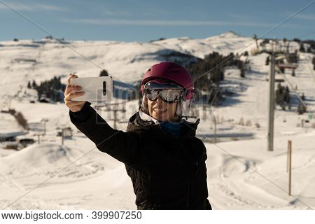 Young Girl With Ski Clothes, A Pair Of Ski Goggles And A Ski Helmet Making A Selfie In A Ski Resort