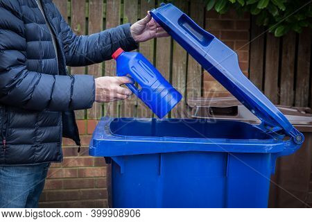 A Responsible Man Placing A Blue Plastic Bottle Into A Kerbside Recycling Bin Ready For Collection A