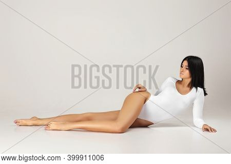 Gorgeous Healthy Woman With Perfect Body And Beautiful Long Legs In White Bodysuit Posing Over Studi