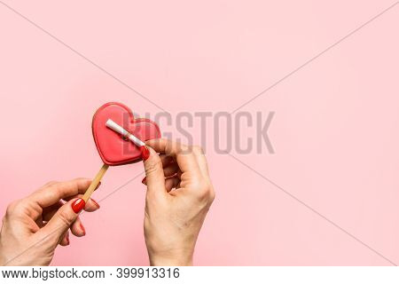 Woman Unfolds A Love Note On Heart Shaped Cookie On Pink Background. Greeting Card With Copy Space.