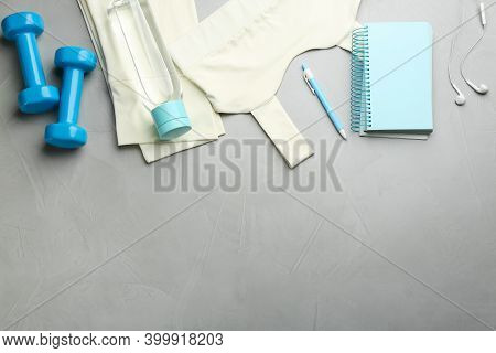 Flat Lay Composition With Sportswear, Notebook And Dumbbells On Grey Background, Space For Text. Gym