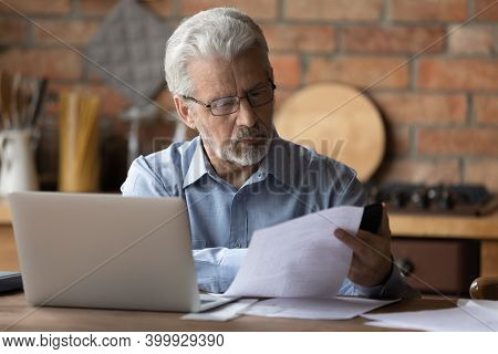 Focused Middle Aged Man Doing Financial Paperwork At Home.