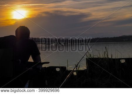 Angler, Hobby And Rest By The Lake At Sunset