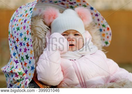 Sad Crying Hungry Baby Girl Sitting In The Pram Or Stroller On Cold Autumn, Winter Or Spring Day. We