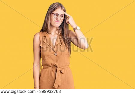 Young beautiful blonde woman wearing casual clothes and glasses pointing unhappy to pimple on forehead, ugly infection of blackhead. acne and skin problem