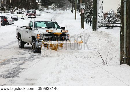 NORWALK, CT, USA - DECEMBER 17, 2020: Snow plowing truck on Taylor Avenue after winter snow storm.