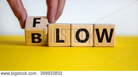 Blow Or Flow Symbol. Male Hand Turns A Cube And Changes The Word 'blow' To 'flow'. Beautiful Yellow