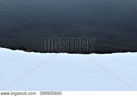 The Lake Shore Is Covered With Snow. Snow And Water. A Clear Boundary Between Water And Snow. The Fi