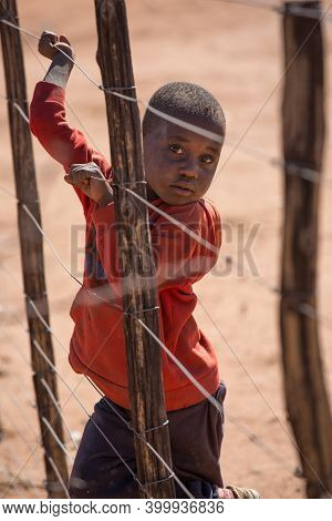Namibia, Africa, Himba Village, July 18, 2019: A Dark-skinned Boy Stands Behind A Barbed Wire Fence.