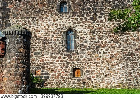 The Fortified Stone Wall Of The Old Castle With Small Windows And A Turret.