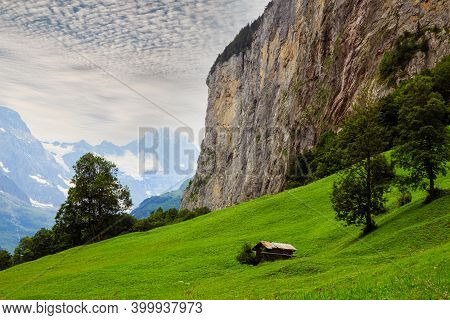 Beautiful Alpine Landscape With Fresh Green Pasture And Steep Cliffs In The Lauterbrunnen Valley On