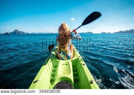 Woman Paddling A Kayak At Sea With Distant Mountains Ahead. Kayaking In El Nido, Palawan, Philippine