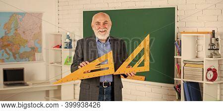 Solve Mathematical Problems. Mature Man Teacher Use Math Triangle Tool. Bearded Tutor Man At Blackbo