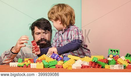 Importance Of Playing Together. Bearded Hipster And Boy Play Together. Dad And Child Build Plastic B