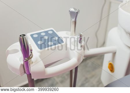 Metallic Dentist Tools Close Up On A Dentist Chair In Dentist Clinic.