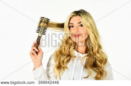 Rom Dream To Reality. Girl Care Of Hairstyle. Woman Curling Hair With Straightener. Woman Styling Ha