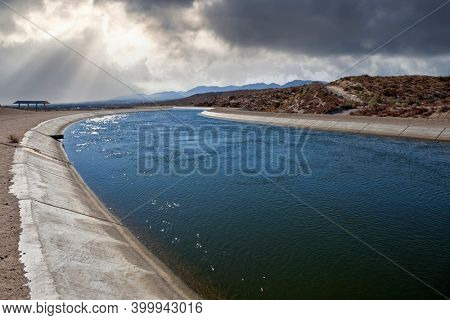 View of the California Aqueduct water canal with storm sky in the Mojave desert.