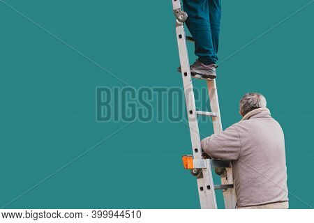Worker Holds Folding Ladder To Insure His Partner To Not Fall. Blue Background. Copy Space. Repair.