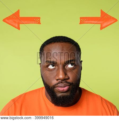 Confused Black Man Has To Choose The Right Arrow To Follow. Concept Of Options, Confusion, Decision.