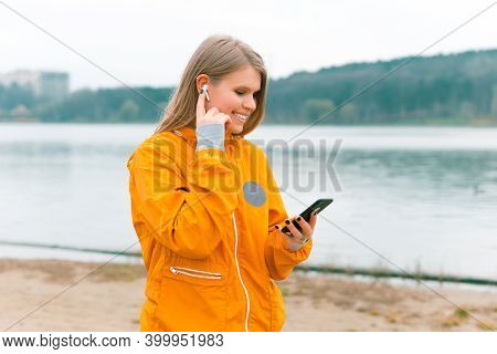 Sporty Woman Is Walking And Using Her Earpods And Phone Near A Forest Lake.