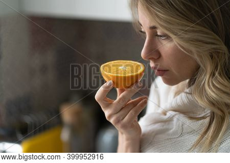 Sick Woman Trying To Sense Smell Of  Half Fresh Orange, Has Symptoms Of Covid-19, Corona Virus Infec