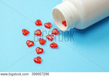 Cardiology Pills. Red Pills In The Shape Of Heart With Bottle On Blue Background
