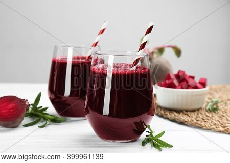 Fresh Beet Juice And Raw Vegetable On White Wooden Table