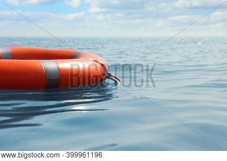 Orange Life Buoy Floating In Sea. Emergency Rescue Equipment