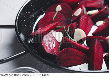 Slices Of Raw Beetroot With Garlic And Rosemary In Wok Pan On White Table, Closeup