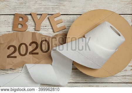 Flat Lay Composition With Text Bye 2020 And Toilet Paper On White Wooden Table, Flat Lay
