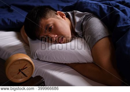 A Depressed Young Man Suffering From Insomnia Lying In Bed