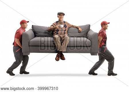 Movers carrying an elderly man with a cup of tea seated on a sofa isolated on white background