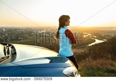 Young Woman Standing Near Her Car Enjoying Warm Sunset View. Girl Traveler Leaning On Vehicle Hood L