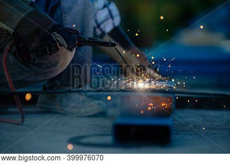 Closeup Hand Of Welder In Safety Gloves Welding Steel In Site Work. Welder Wearing Safety Glove For