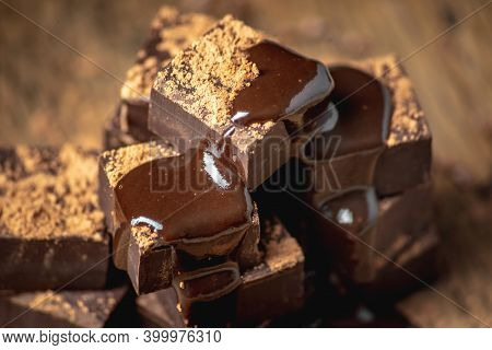Delicious Appetizing Dark Chocolate Bars Of A Square Shape Are Stacked In A Tower And Poured With Li