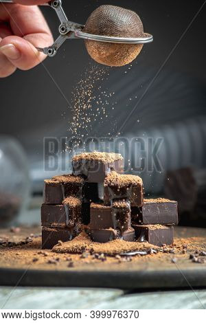 Hand Is Sprinkling Cocoa Powder On Delicious Appetizing Cubes Of Bitter Dark Chocolate