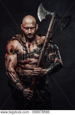 Serious And Furious Barbarian With Bald Head And Grimy And Bloody Skin In Armour With Fur Posing In