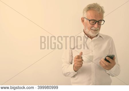 Studio Shot Of Handsome Senior Bearded Man Holding Coffee Cup While Using Mobile Phone With Eyeglass
