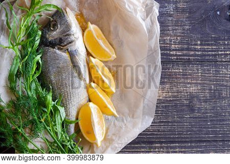 Gilthead With Lemon And Greens, On The Background Of A Wooden Table